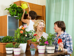 pensioners  and girl  watering decorative plants