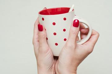 mains de femme tenant un mug