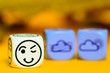 concept of autumn weather - emoticon and weather dice on orange