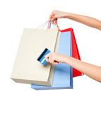 hands holding colored shopping bags on white background