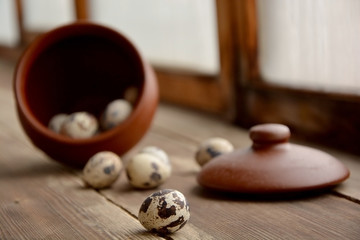 Quail eggs in a ceramic pot, one egg in focus