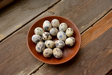 Fresh quail eggs in a ceramic plate on a wooden background