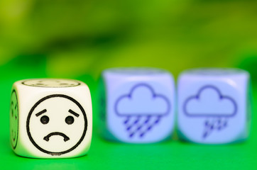 concept of sad storm weather - emoticon and weather dice on gree
