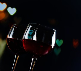 red wine glasses on hearts decoration bokeh lights background