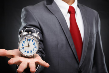 Time is money.Business man holding clock against dark background