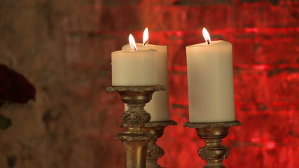 Lighted candles in golden candlesticks, close-up