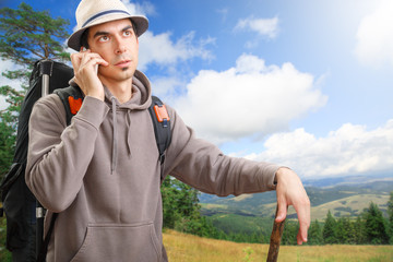 Young man talking on the phone in the nature on mountain