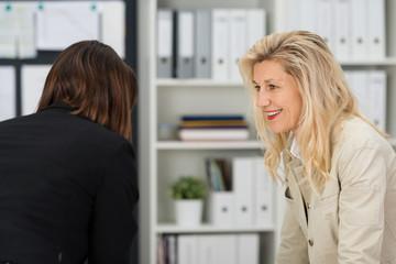 gespräch zwischen kolleginnen im büro
