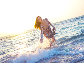 young and beautiful girl splashing water in ocean in sunset