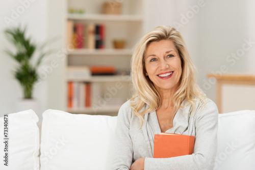 Leinwanddruck Bild entspannt lächelnde best-ager frau auf dem sofa