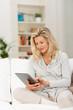 Leinwanddruck Bild entspannte frau tippt zuhause auf dem tablet-pc