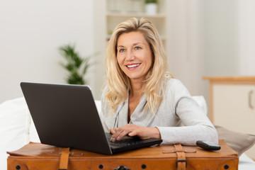 lächelnde frau bucht eine reise am laptop