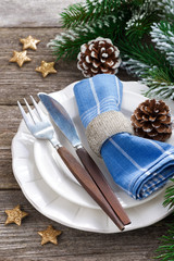 Christmas table setting with spruce branches and stars on wood