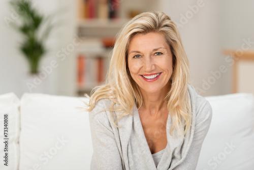 entspannte ältere frau sitzt auf dem sofa in ihrer wohnung - 73340808