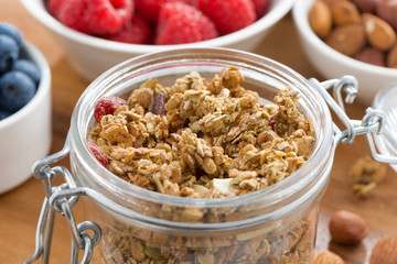 glass jar with homemade granola and fresh berries, close-up