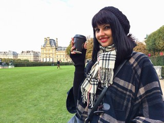 young beautiful brunette enjoys cup of coffee in Paris
