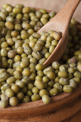 Green mung bean in a wooden bowl with spoon close-up.