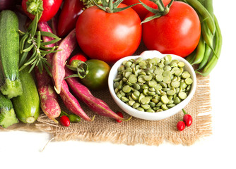 Green peas in and vegetables on a white background