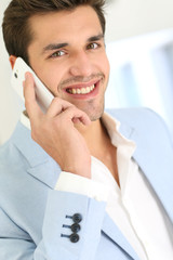 Smiling attractive young man talking on the phone