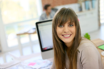 Portrait of young woman sitting in front of desktop computer