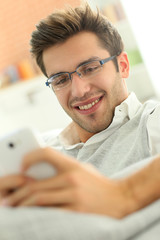 Casual guy using smartphone, relaxing in couch