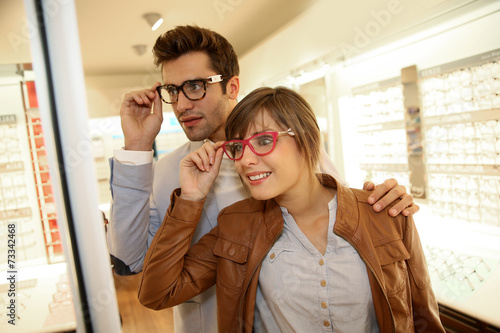 Couple in optical shop choosing eyeglasses - 73342468