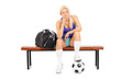 Worried female football player sitting on a bench