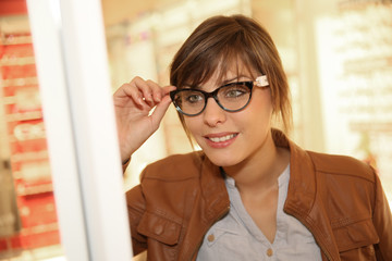 Young woman in optical store trying eyeglasses on