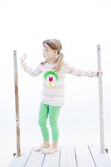 mädchen mit clown-sweater und grüner hose