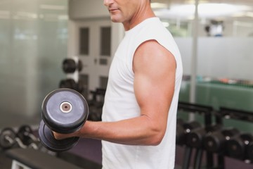 Fit man lifting heavy black dumbbell