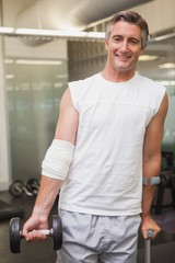 Injured man holding dumbbell in the weights room