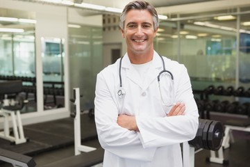 Confident doctor standing in weights room