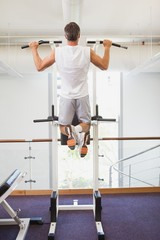 Fit man doing pull ups in fitness studio