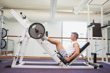 Fit man lifting heavy barbell with legs