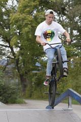 Junger Mann springt mit dem Fahrrad über eine Rampe