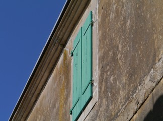 A house with green wooden shutters in Betina in Croatia