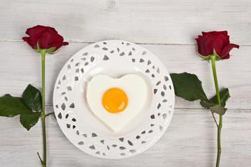 Herzförmiges Spiegelei auf weißen Teller mit roten Rosen