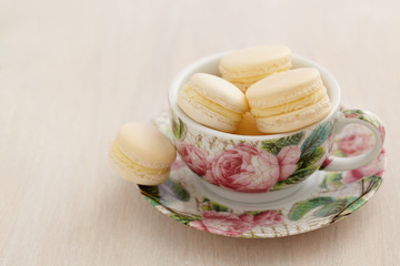 Macarons in Teetasse mit Rosenmuster