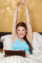 Junge Frau benützt Tablet PC im Bett