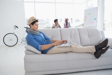 Young creative man using laptop on couch