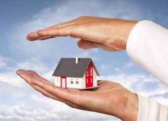 Haus wird mit Händen geschützt