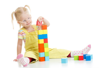 Child in eyeglases playing building blocks isolated