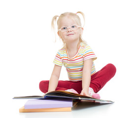 Funny smiling child in eyeglases reading book isolated