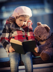 Little girl reads the book to a toy bear, toning, vignetting