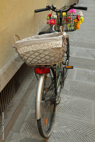 Staande foto Fiets city bike with romantic basket parked by wall in Florence