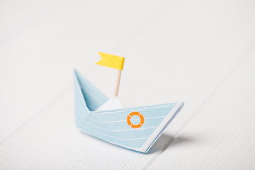Blaues Papierboot mit gelber Flagge