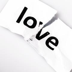"""""""Love"""" word written on torn paper"""