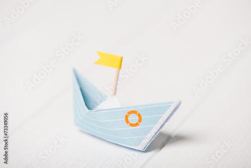 canvas print picture Blaues Papierboot mit gelber Flagge