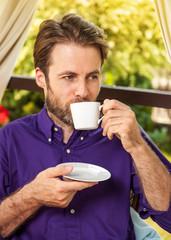 Man drinking morning coffee outdoor on garden terrace