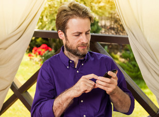 Man looking at mobile phone outdoor on garden terrace